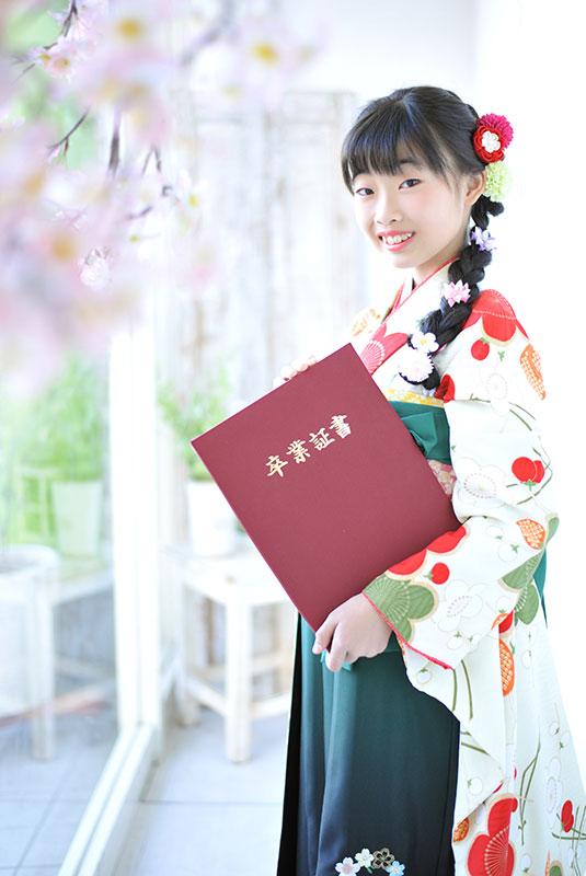 卒業袴 小学校 着物 クリーム色 袴 緑 卒業証書と 桜 自然光